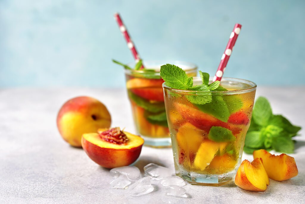 Peach iced tea with mint in a glass on a light background.